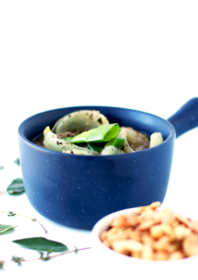 Onions and leeks in a homemade broth in a blue ceramic soup bowl, surrounded by fresh thyme sprigs, sage leaves, and cashews.