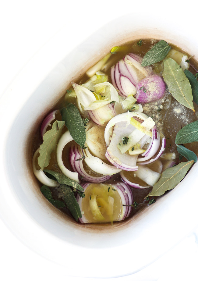 Onions, leeks, sage leaves, thyme sprigs, and bay leaves in a slow cooker.