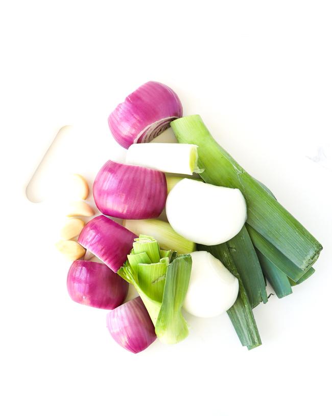 Onions, leeks, and garlic on a white cutting board.