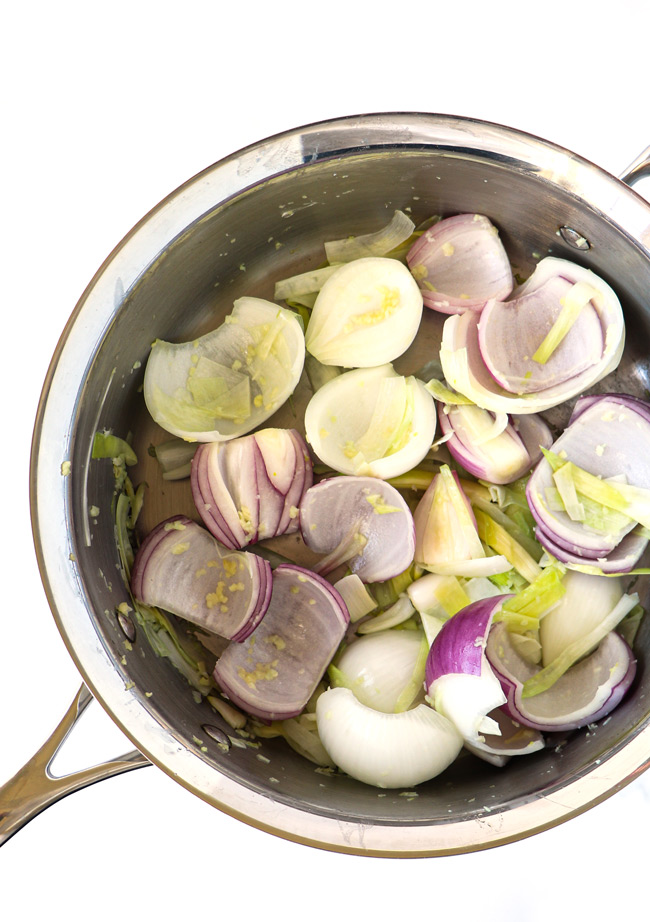 Onions, leeks, and garlic in a stainless steel sauté pan.