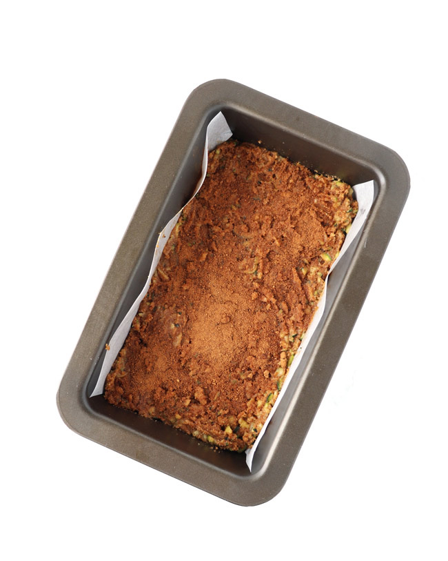 Paleo Zucchini Bread dough in a parchment-lined metal loaf pan on a white marble surface.