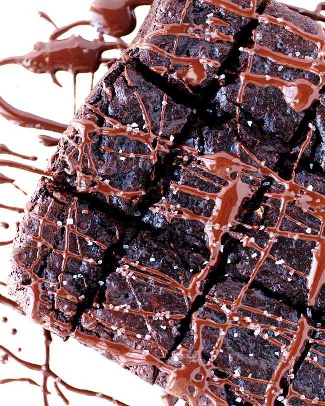 Paleo Zucchini Brownies drizzled in chocolate and sprinkled with coarse sea salt on a white cutting board.