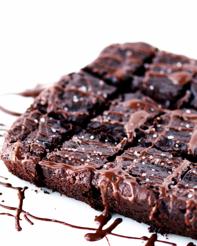 Paleo Zucchini Brownies drizzled in chocolate and sprinkled with coarse sea salt on a white marble surface.