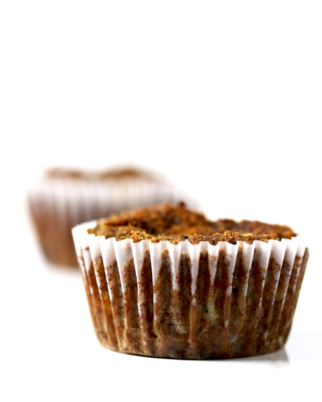 Paleo Zucchini Muffins in white paper muffin cups on a white marble surface with a white background.