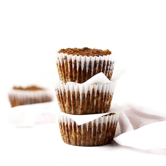 Paleo Zucchini Muffins in white paper muffin cups stacked on top of each other with a white napkin nearby on  a white marble surface.