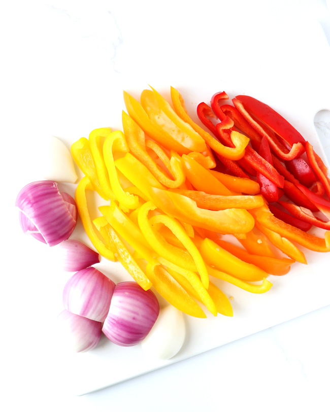 Red, orange, and yellow bell peppers with white and red onions on a white cutting board.