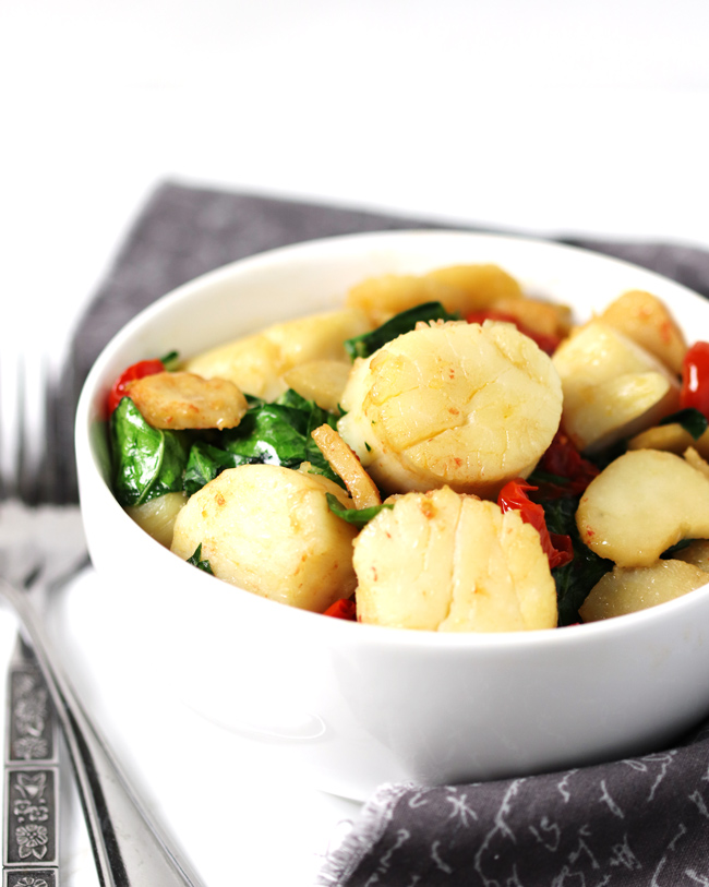Sea Scallops, water chestnuts, and bok choy in a white porcelain bowl with silverware and a gray napkin.