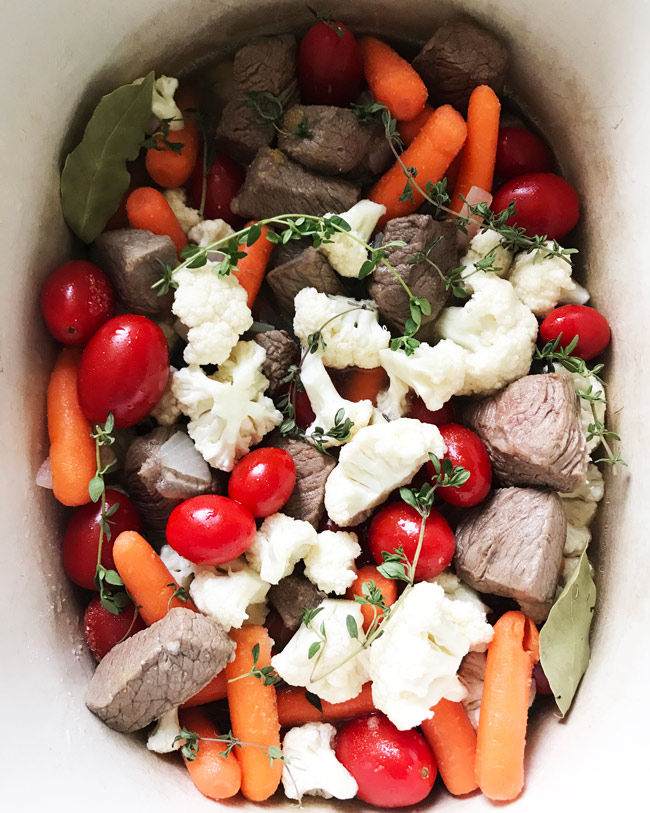 Beef stew ingredients, including stew meat, carrots, cauliflower, and tomatoes with bay leaves and thyme sprigs in a slow cooker.