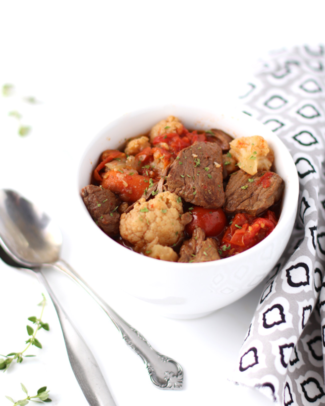 Beef Stew with tomatoes and cauliflower in a white porcelain mug with silverware, fresh thyme, and a black, gray, and white napkin to the side.