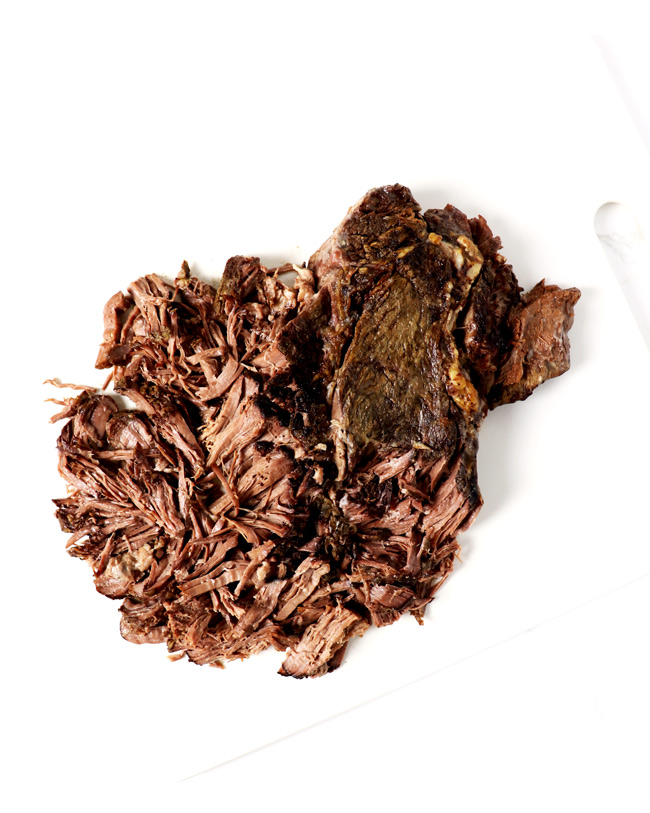 Shredded beef on a white cutting board on a white marble surface.