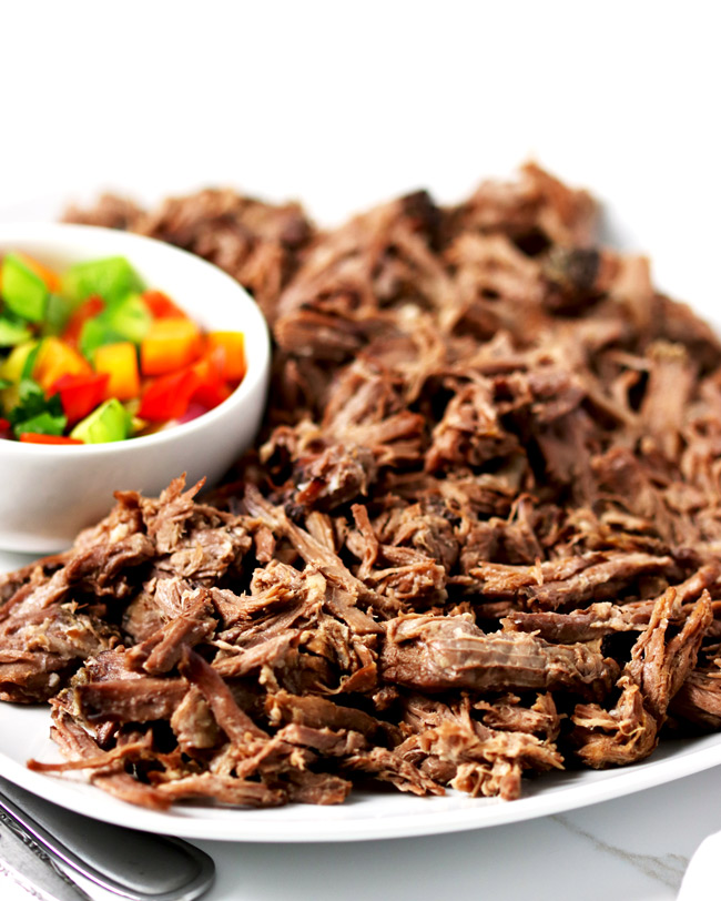 Shredded beef on a white porcelain plate, surrounded by a white napkin, sliced green onions, and fresh pico de gallo.