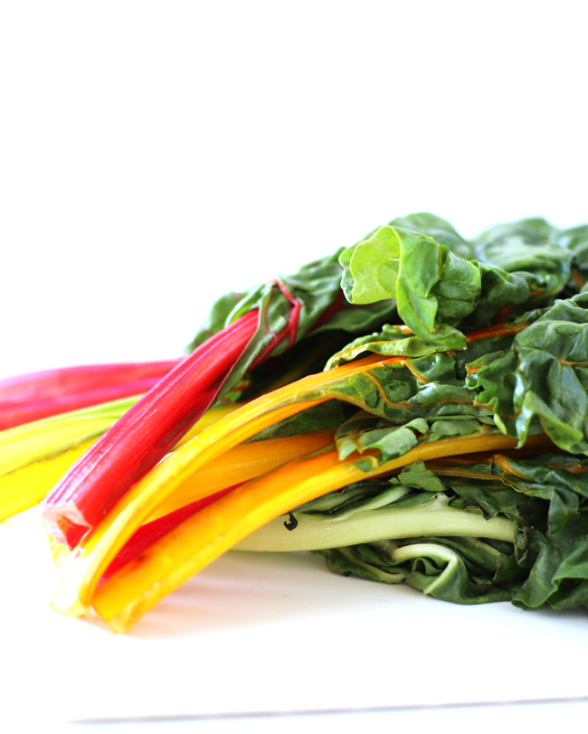 Close-up of rainbow chard on a white cutting board.
