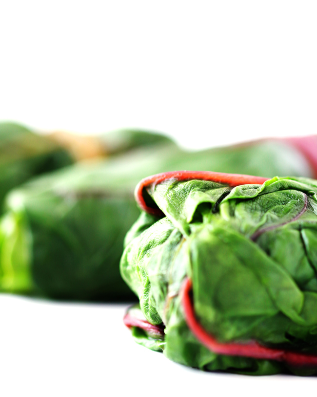 Close-up of a Rainbow Swiss chard leaf rolled into a grain-free wrap recipe.