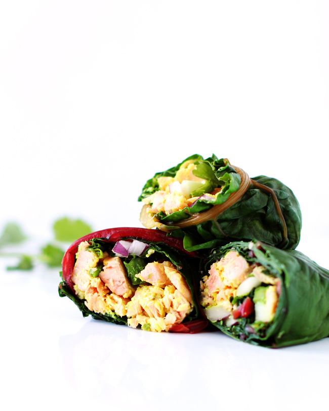Three rainbow chard Spicy Salmon Roll-ups on a white marble surface with fresh cilantro leaves in the background.