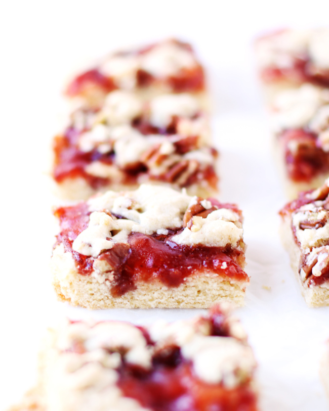 Strawberry Jam Bars in a row on a piece of white parchment.