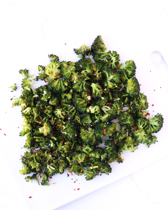 Roasted broccoli with red pepper flakes on a white cutting board.