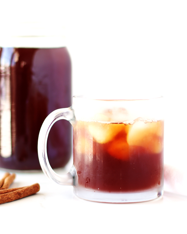 Black tea poured over ice in a clear coffee mug with black tea in the background and cinnamon sticks in the foreground.