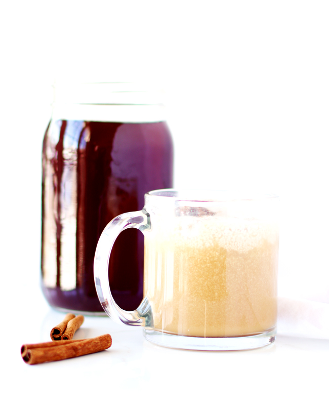 Chai Iced Tea ingredients stirred together in a clear coffee mug with black tea in the background and cinnamon sticks to the left.