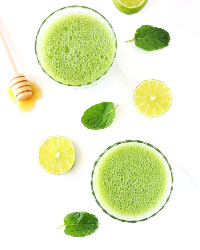 Cucumber Mint Coolers with fresh mint leaves, drizzled honey, and slices of lime on a white marble surface.