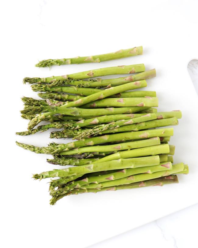 Fresh asparagus stalks on a white cutting board.