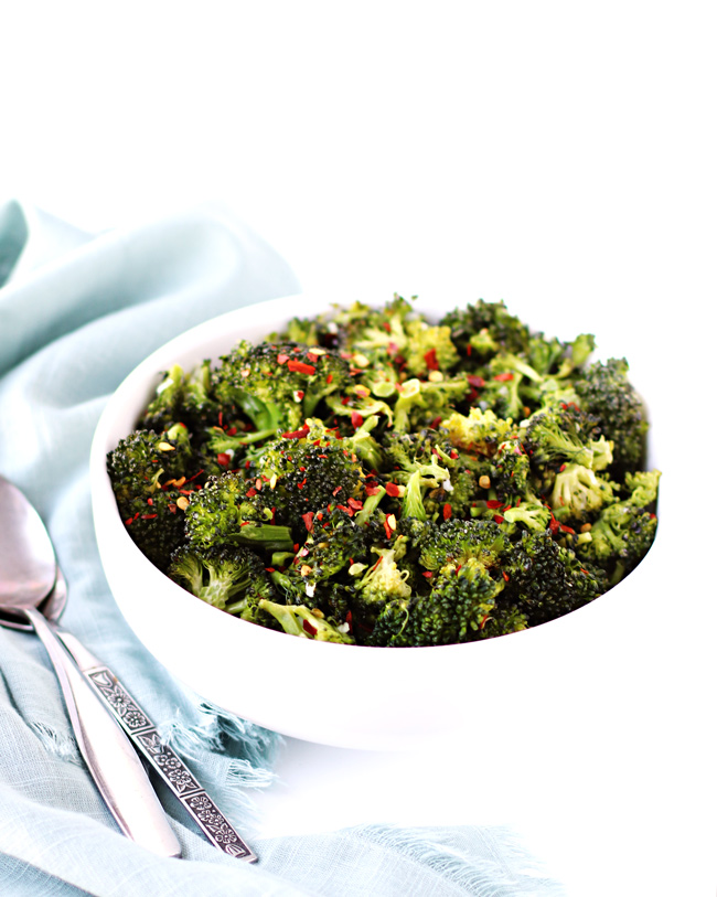 Roasted broccoli with red pepper flakes in a white porcelain bowl with a light blue-green napkin and shiny silverware.