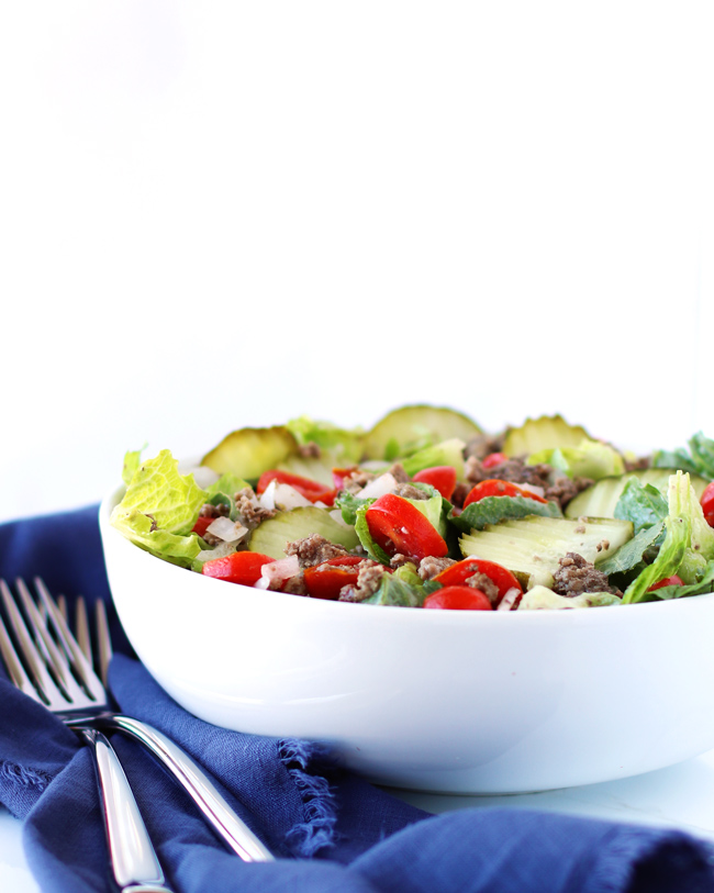 Eye-level photograph of hamburger meat mixed with tomatoes, onions, garlic, and dill pickles in a white bowl on topic of a blue napkin next to silverware.