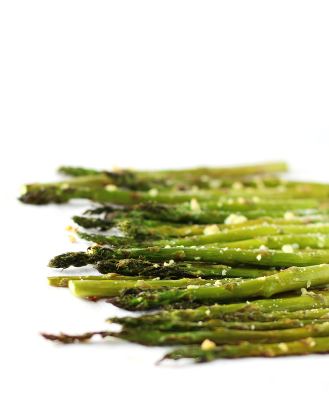Eye-level photograph of roasted asparagus topped with sea salt and garlic.