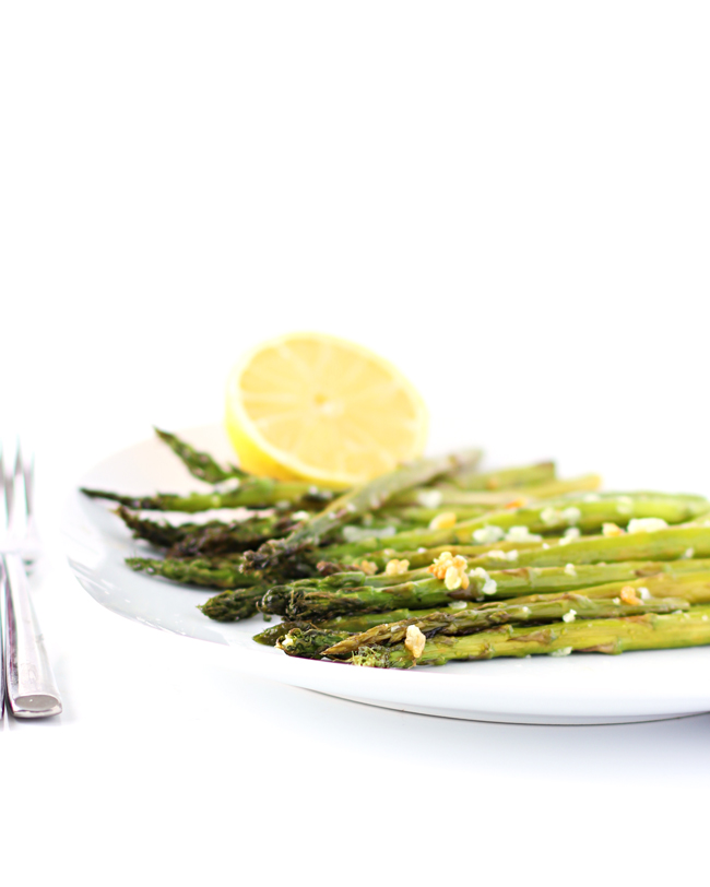 Roasted asparagus topped with garlic and sea salt with a lemon wedge and silverware.