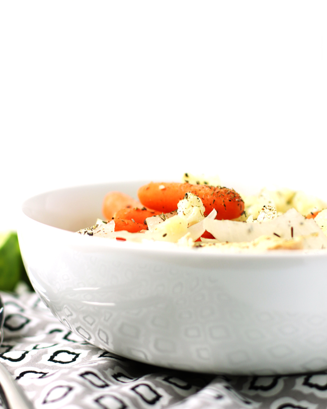 Chicken, onions, carrots, and cauliflower in broth in a white bowl next to fresh limes, silverware, and a gray, black, and white napkin.