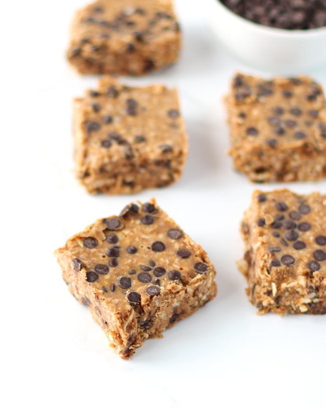 Chocolate chip coconut dessert bars on a white marble surface next to a small bowl of allergen-friendly chocolate chips.