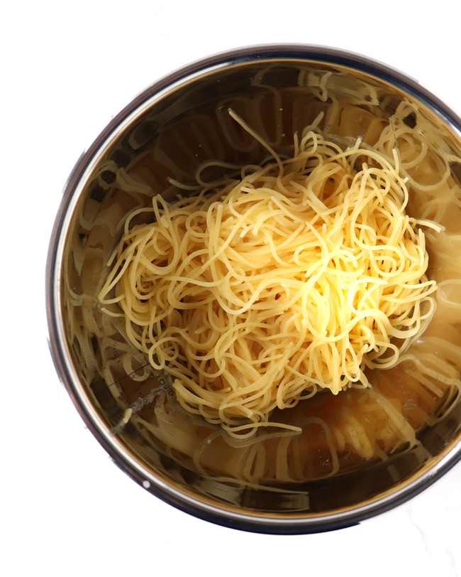 Gluten-Free Lemon garlic Pasta in a stainless steel bowl on a white marble surface.