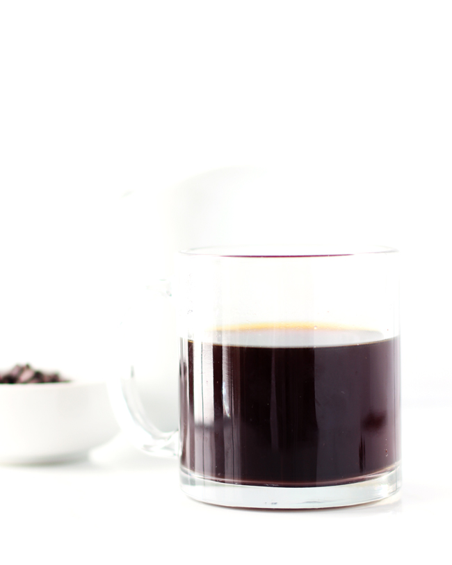 A fresh cup of black coffee in a clear glass mug in front of a small dish of allergen-friendly chocolate chips.