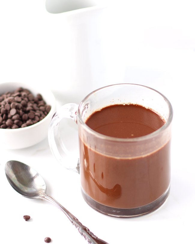 Chocolate coffee in a clear glass mug with chocolate chips sprinkled nearby.
