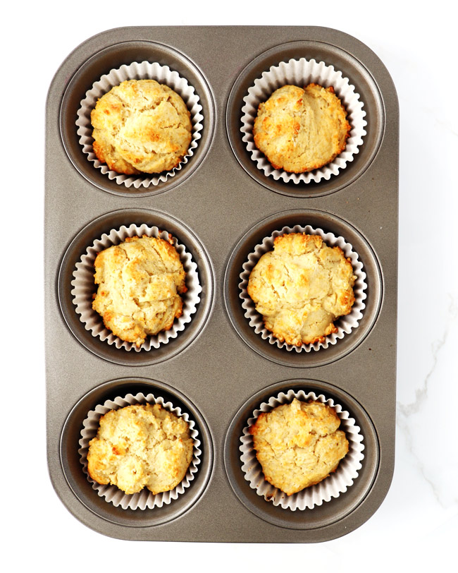 Baked gluten-free muffins a muffin pan on a white marble surface.