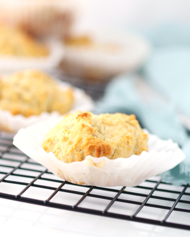 Muffins in white paper cups on a black cooling rack with a light green napkin in the background.