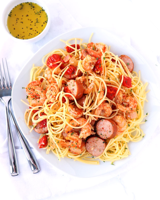 Gluten-free spaghetti with cooked shrimp and sausage on a white plate with a white napkin.