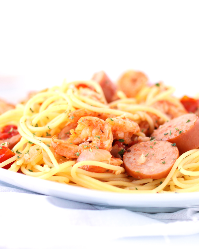 Close-up, eye-level picture of spaghetti, shrimp, and sausage on a white plate with a white napkin.