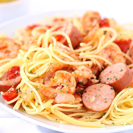 Close-up image of shrimp, onions, tomatoes, and sausage with gluten-free spaghetti on a white plate with a white napkin.