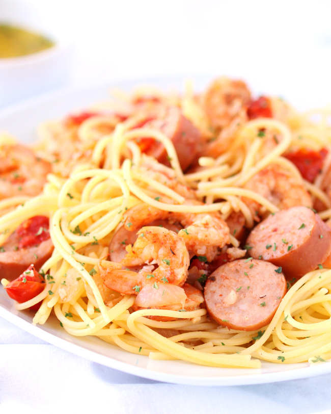 Close-up image of shrimp, onions, tomatoes, and sausage with gluten-free spaghetti on a white plate with olive oil in the background.