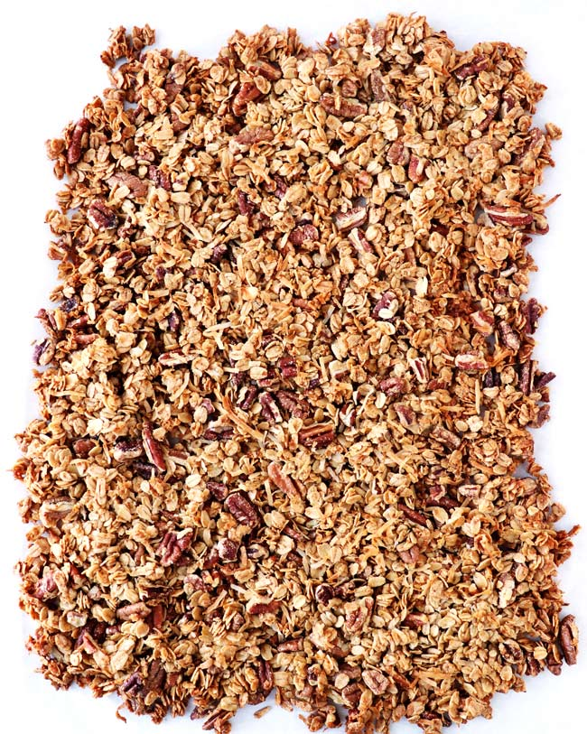 Baked gluten-free Sweet Crunchy Granola on a baking sheet lined with parchment paper.