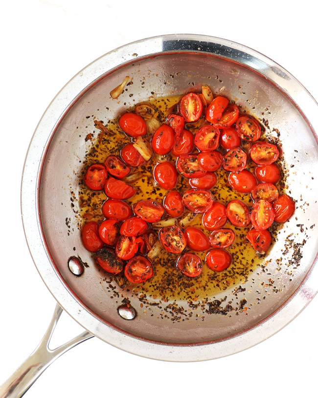 Fresh tomatoes, garlic, and basil sautéing in a stainless steel skillet on a white background.