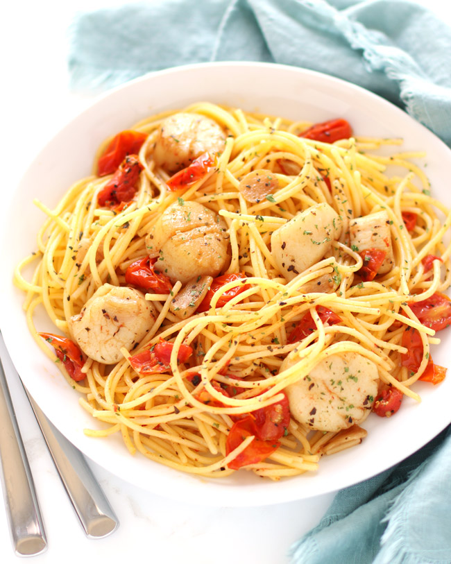 Sea scallops, tomatoes, garlic, and pasta on a white dish with a blue-green napkin and silverware.