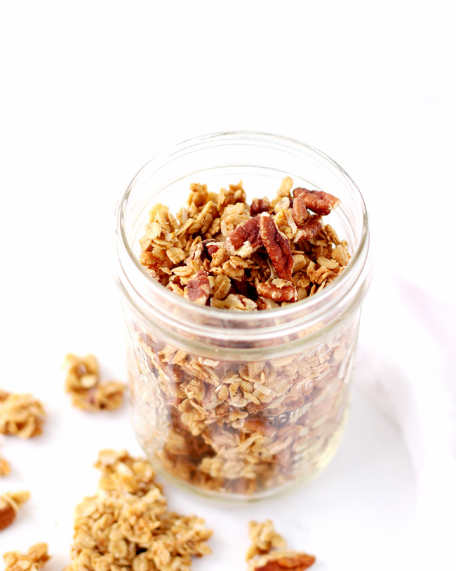 Gluten-free oats, pecans, and shredded coconut in a glass mason jar on a white marble surface, surrounded by granola clusters.