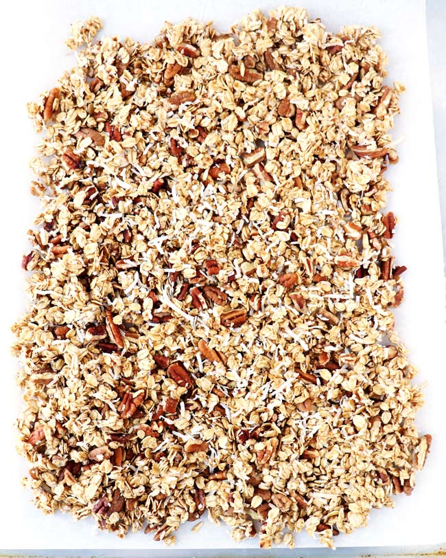Fresh gluten-free granola ingredients including pecans and shredded coconut on a flat baking sheet.