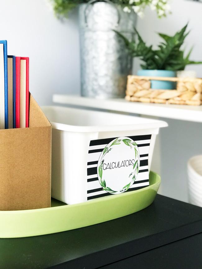 Festive Farmhouse classroom decor supply labels on a white tray next to a kraft book bin.